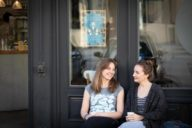 Café owner Stephanie Bjarnason and writer Anika Landsteiner sit in front of Café Blá.