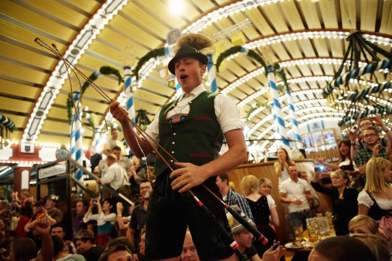 A man dressed in a traditional costume is celebrating and dancing on a table in a beer tent at the Oktoberfest in Munich.