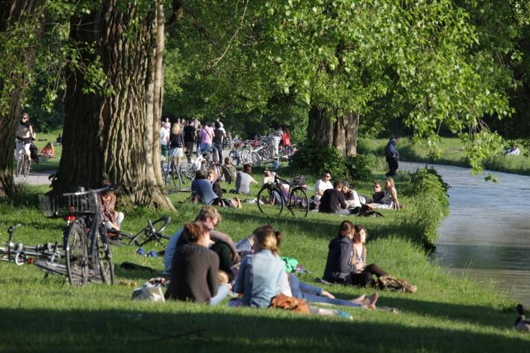 People sitting on the banks of the Eisbach in the Englischer Garten in Munich.