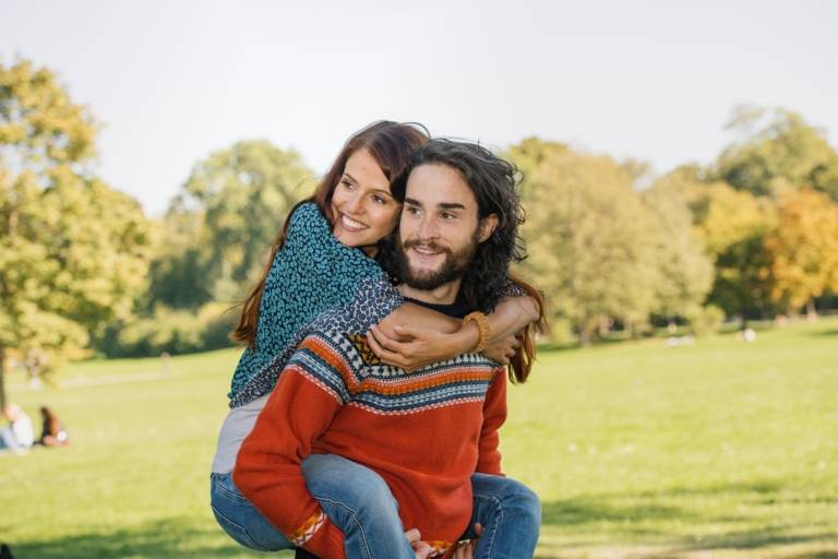 A young man is giving a woman a piggyback in the Englisch Garden in Munich.