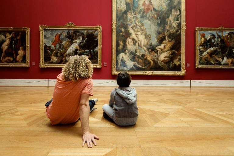 A young man and a boy are sitting on the ground in front of paintings in the Alte Pinakothek in Munich.