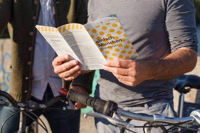 A man is holding a city map in his hands. A bike is besides him.