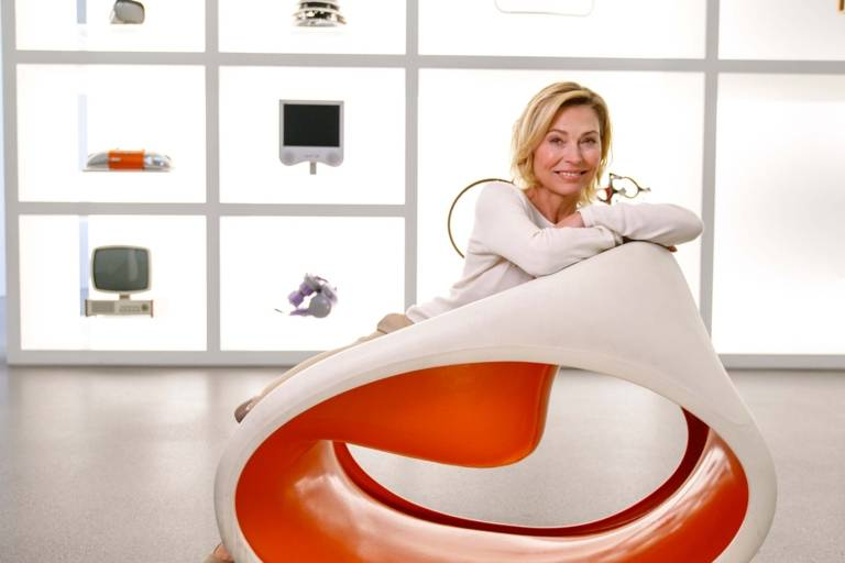 A woman is sitting on a chair in front of a vitrine with exhibits in the Pinakothek der Moderne in Munich.
