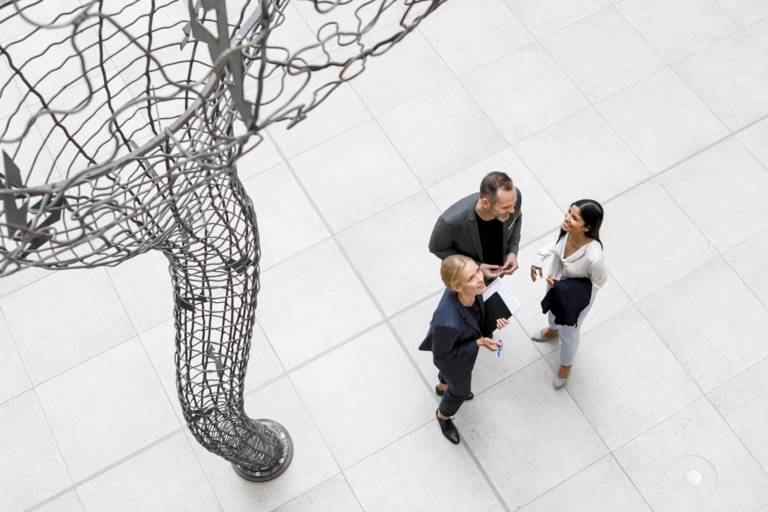 Two women and a man are talking besides a huge sculpture in Munich.