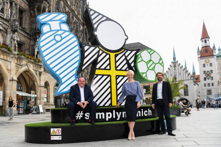 Sports Officer Florian Kraus, Mayor Katrin Habenschaden and Clemens Baumgärtner, Officer for Employment and the Economy, stand in front of the Spectacular at Marienplatz.