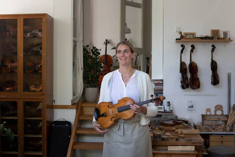 Violin maker Katharina Starzer stands in her workshop with a violin in her hands