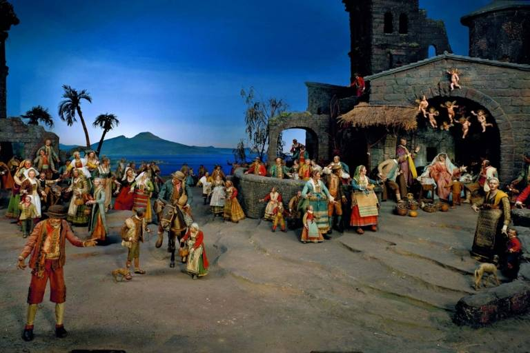 Nativity scene with figures in front of the Gulf of Naples with Vesuvius in the background.