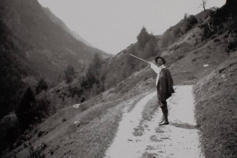 Photo of a black and white shot of a man with a hat walking in the mountains.