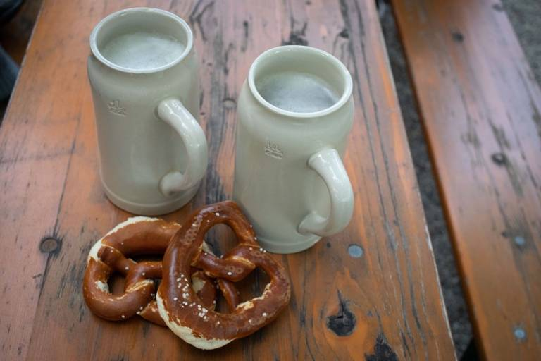 Two beer mugs and two pretzels on a wooden table.
