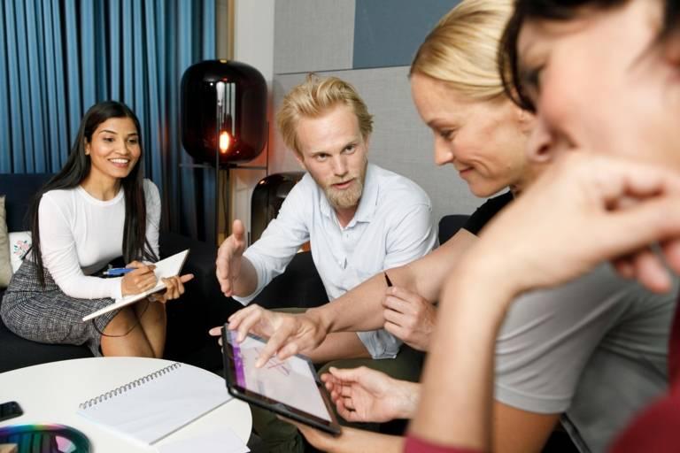 Ein Mann und drei Frauen sitzen für eine Besprechung an einem Tisch.