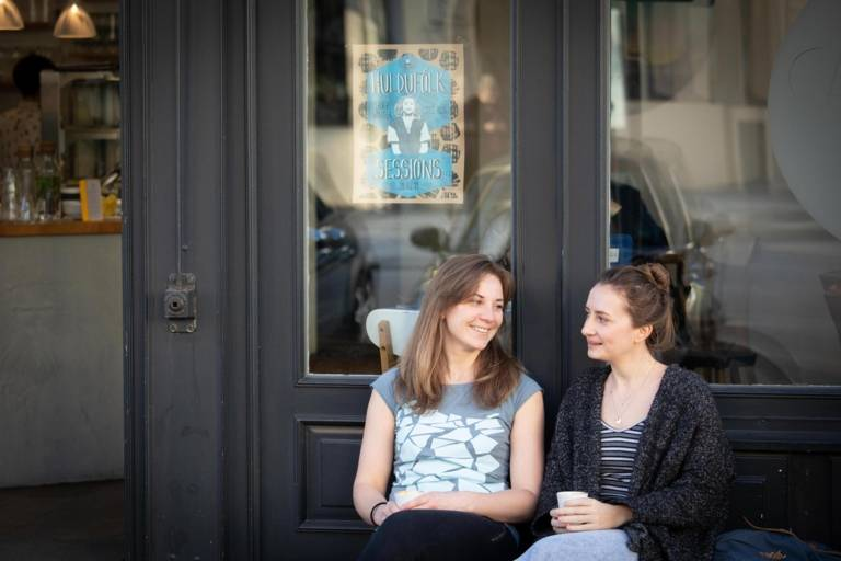 Stephanie Bjarnason and Anika Landsteiner sitting in front of a café.