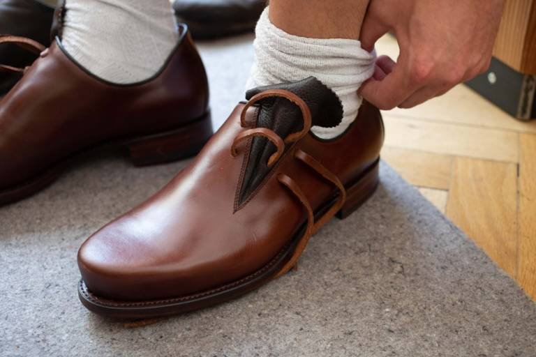 A man tries on a brown traditional leather shoe