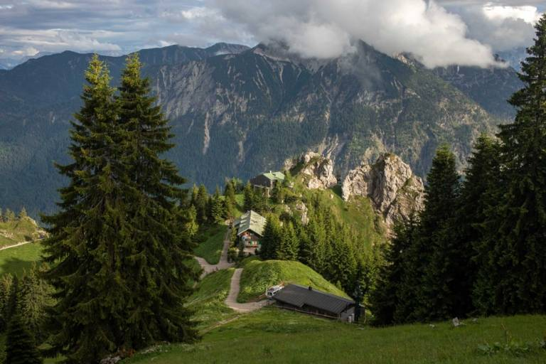 View of an alpine hut in front of a mountain panorama in Munich.