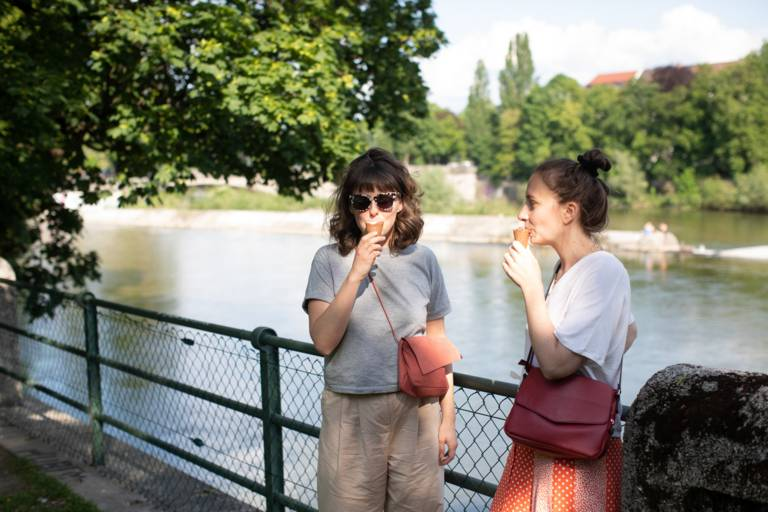 Two women eating ice cream at the Isar in Munich.