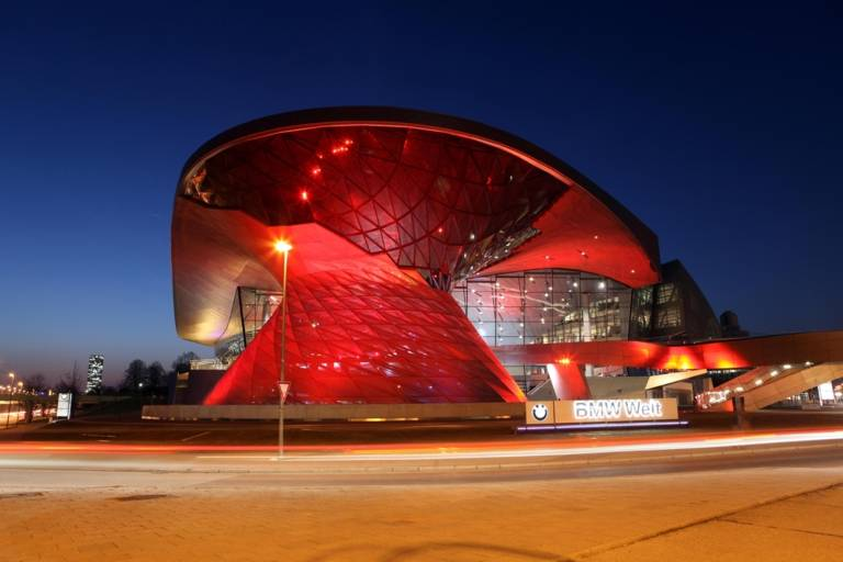 The BMW Welt in Munich illuminated in red at night.
