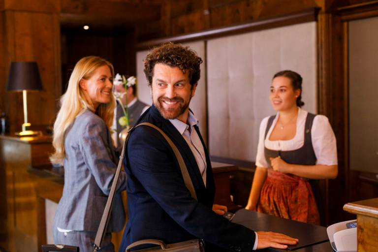 A woman dressed in a dirndl is welcoming a woman and a man in a hotel in Munich.