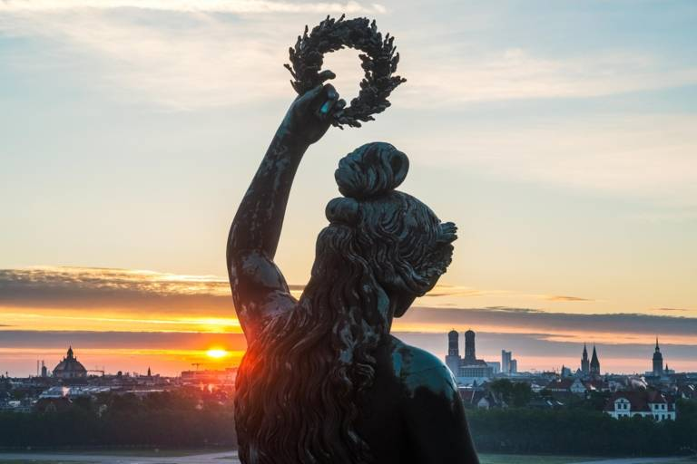 The Bavaria statue at Theresienwiese with Munich's skyline in the background at sunrise.