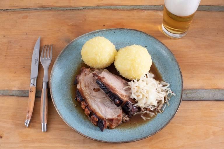 Ein Teller mit Knödeln, Schweinebraten und Krautsalat. Daneben ein Glas Bier.