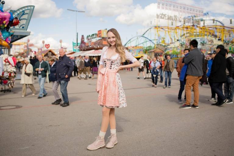 A woman who is wearing a dirndl is smiling at the Oktoberfest in Munich.