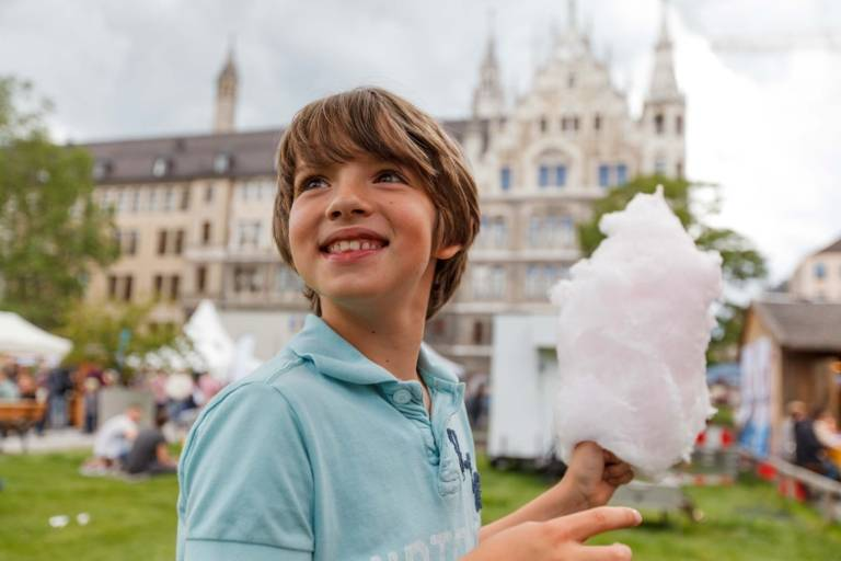 A boy is holding candy floss in his hands at the City Foundation Festival in Munich.