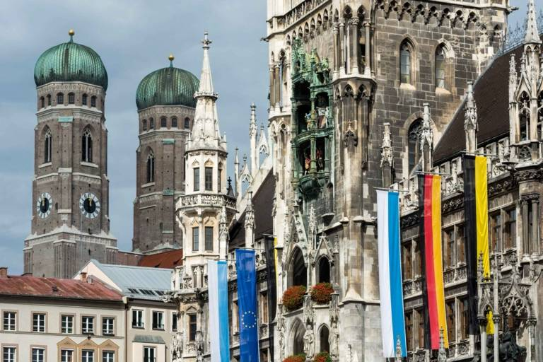 Flags at the Neues Rathaus in Munich with the towers of the Frauenkirche in the background.