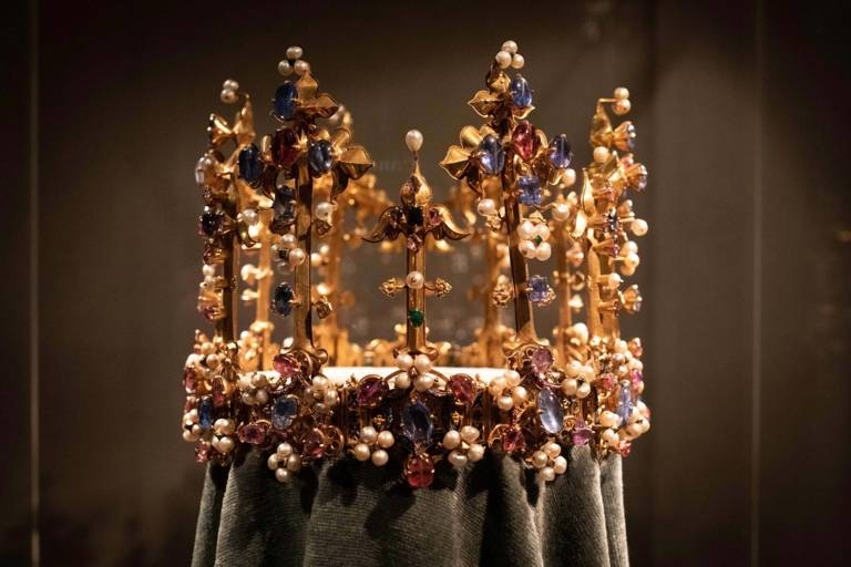 Golden crown with countless gemstones and pearls in the Residence Museum in Munich.