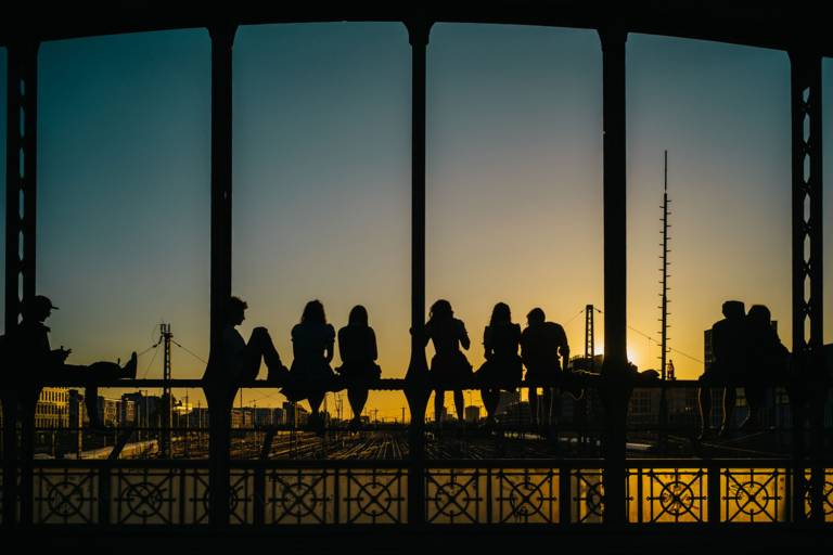 People on the Hackerbrücke in Munich watching the sunset.