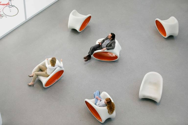 A family is sitting on chairs in front of a vitrine with exhibits in the Pinakothek der Moderne in Munich.