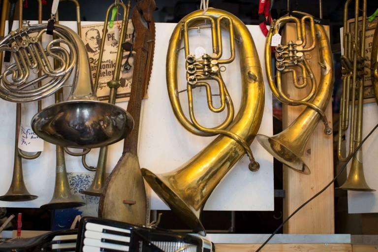 Several wind instruments hang side by side in a music shop