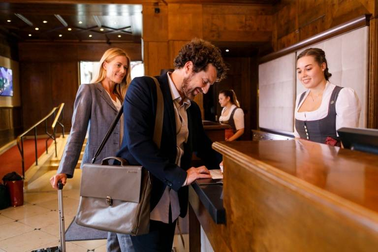 A man and a woman are checking in at a hotel in Munich.
