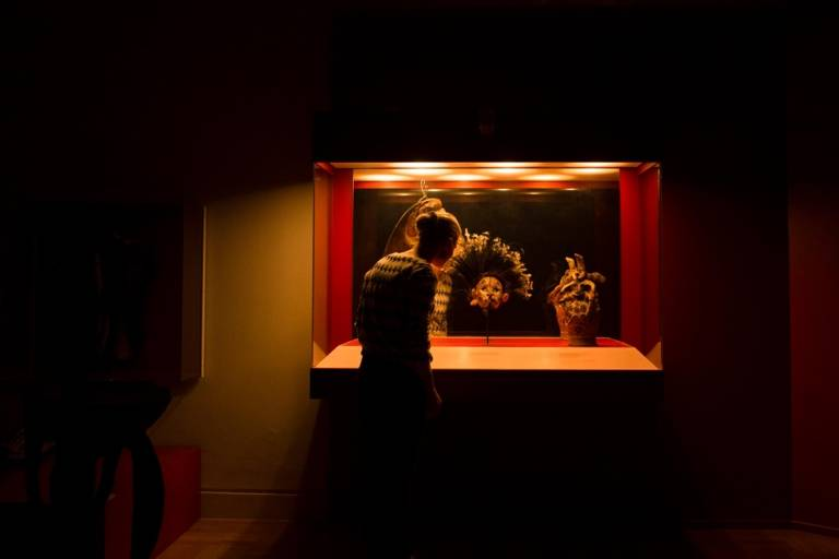 A woman is standing in front of a cabinet full of exhibits in the Museum Museum Fünf Kontinente in Munich.