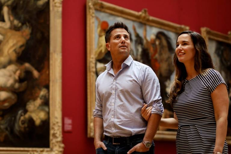 A couple is walking arm in arm through the Alte Pinakothek in Munich and is looking at paintings.
