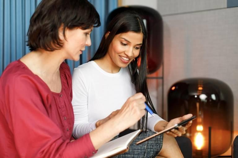 Zwei Frauen diskutieren mit Tablet und Notizblock in der Hand.