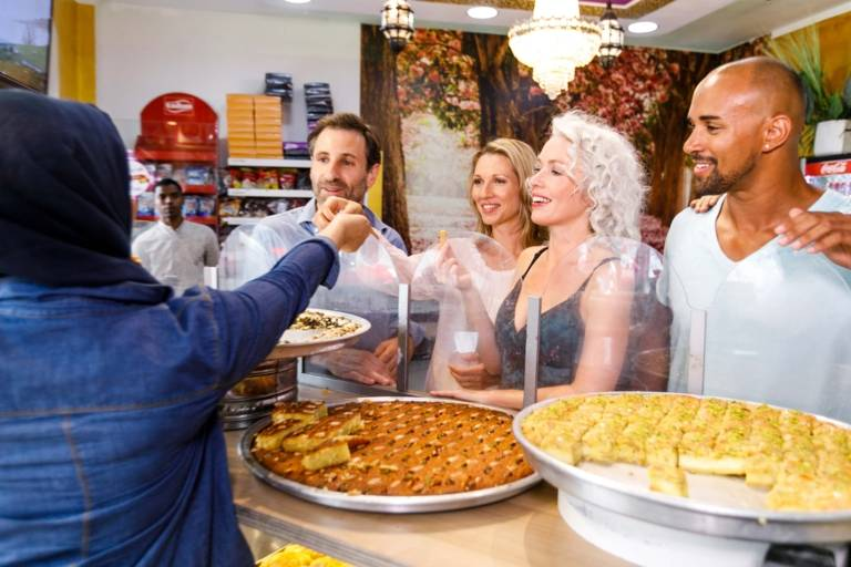 A group of humans is tasting Baklava in front of a vitrine in a shop in the station district in Munich.