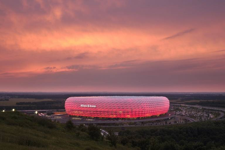 The Allianz Arena in Munich illuminated in red at sunset.
