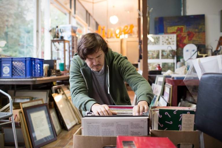 A man is having a look at a box full of records in an antique shop in Munich.