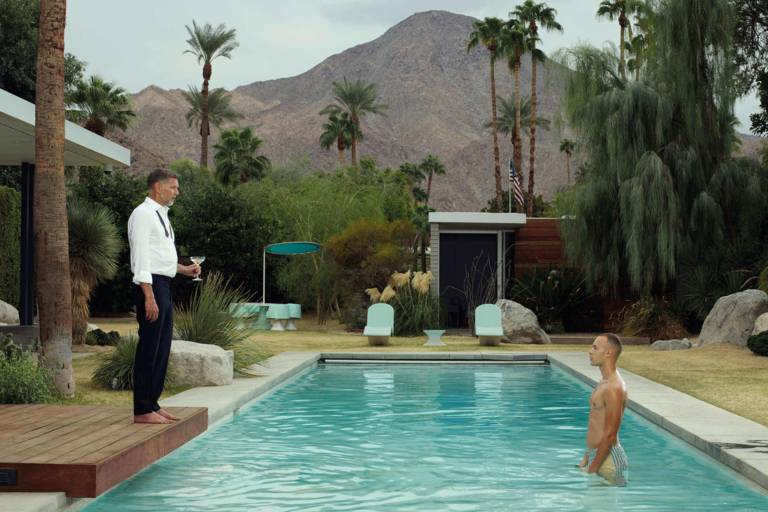 Man in swimming trunks in a pool and man in suit at the edge of the pool in a mountain landscape with palm trees.
