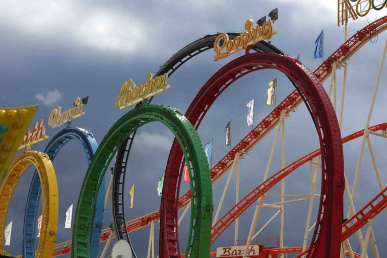 Loops of the roller coaster in the colors yellow, blue-red and green with writing against the blue sky.