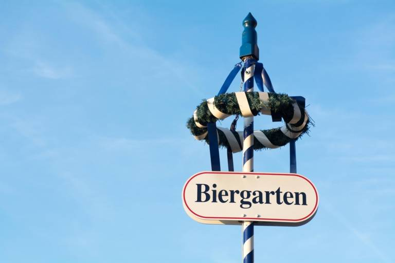 A sign on top of a maypole in Munich that has the word beer garden on it.