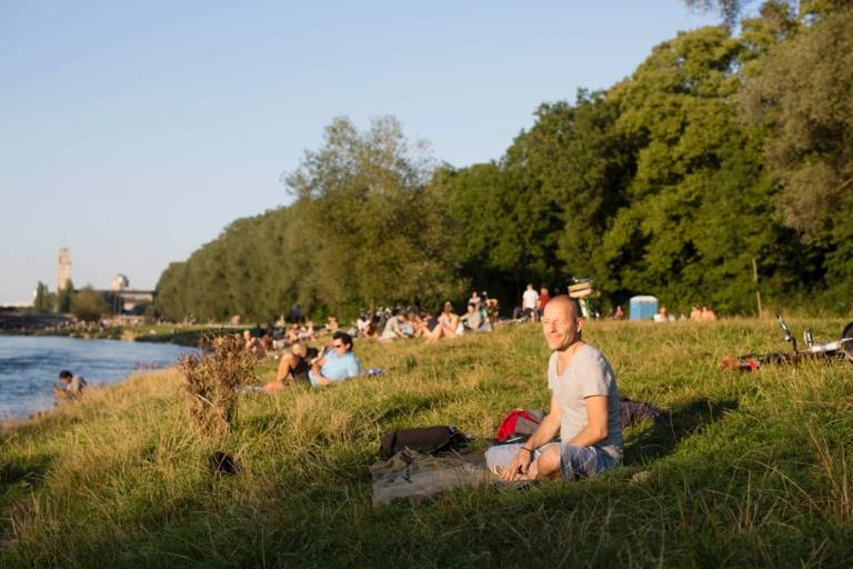 People are sitting on a sunny day at the Isar River Banks in Munich.