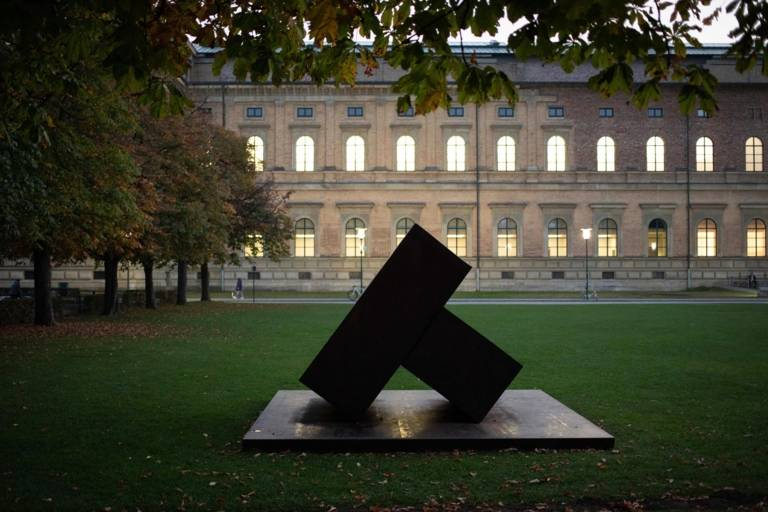 Frontal view of the Alte Pinakothek with trees and a sculpture in front of the building in Munich