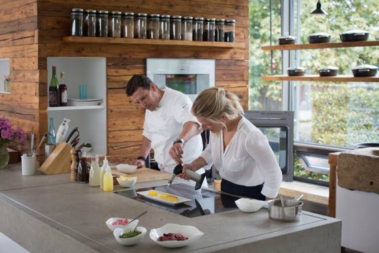 In the cooking school, star chef Christian Jürgens assists the author while flambéing.