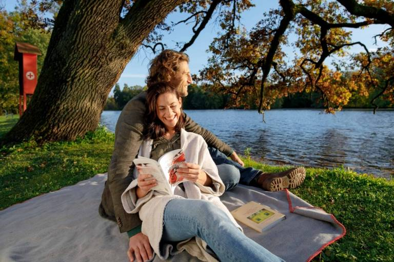A couple is sitting on a picnic blanket at Nymphenburg Schlosspark in Munich on a sunny day in autumn.