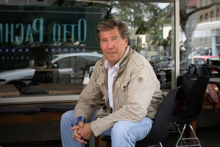 A man sits in front of a café and smiles into the camera.