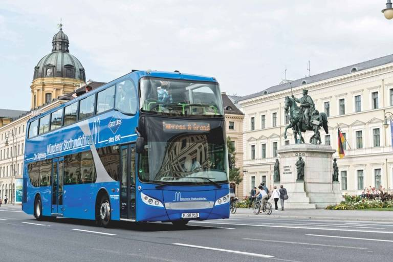 A blue double-decker sightseeing bus from the company GREY LINE is passing the King Ludwig I of Bavaria monument at Ludwigstraße in Munich.