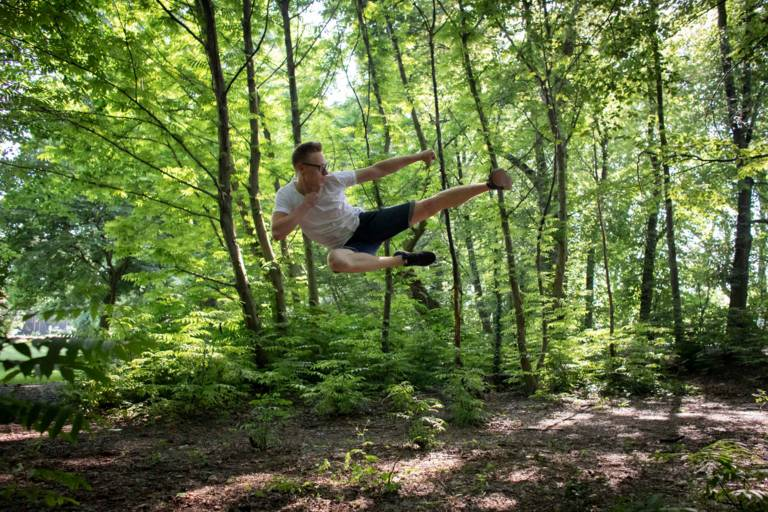 Young man with an action from the Taekwon-Do in a forest in Munich.