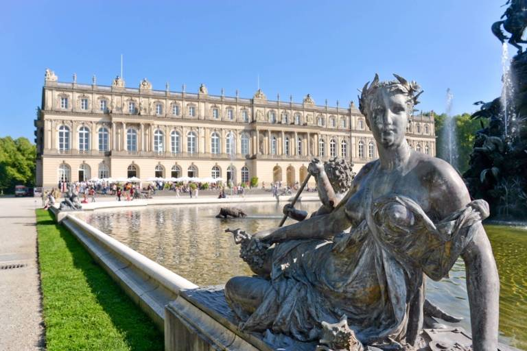 Herrenchiemsee Palace with the fountain and a fountain figure in the front.