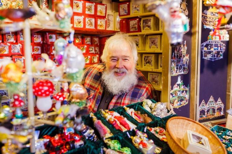 A seller in a sales booth with white hair and a white beard is smiling at the christmas market in Munich.