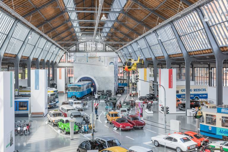 Cars and underground trains are parked in the hall of the transport centre of the Deutsches Museum.