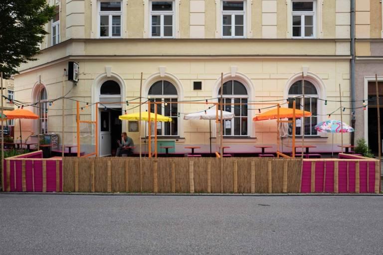 A colourful pub garden with a raffia and bamboo railing in Munich.